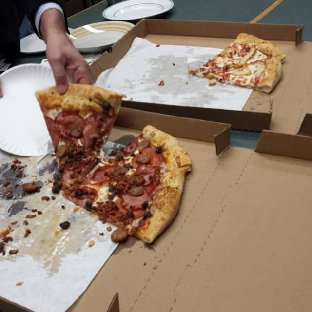 Mike Riscica eating pizza at the office
