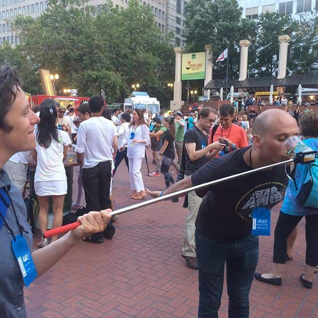 Mike Riscica drinking a beer from a selfie stick