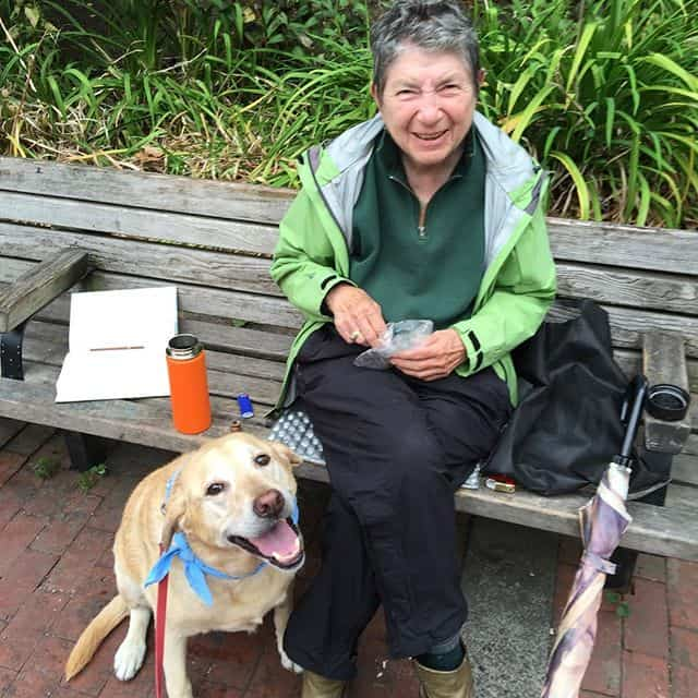 Labrador and lady sitting on a bench