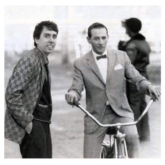 Black and white photo with two men and a bike