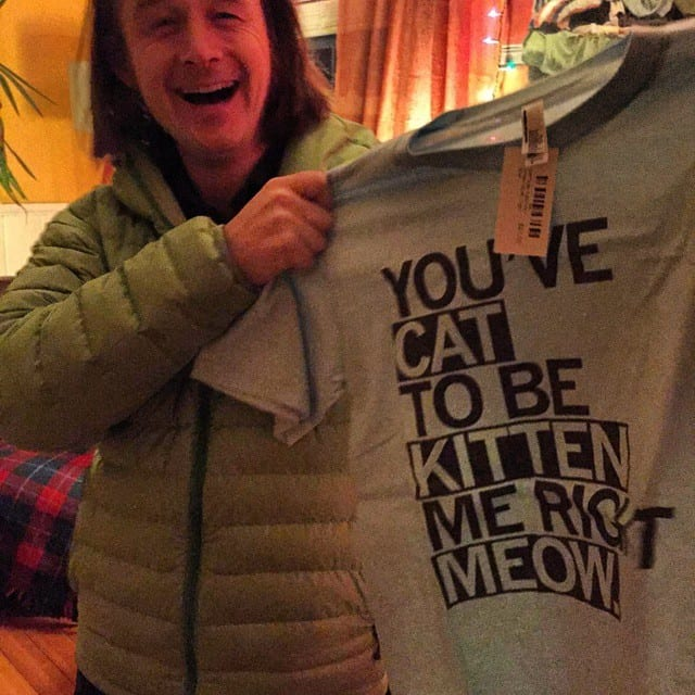 Jamie Obrien holding a funny t-shirt about cats