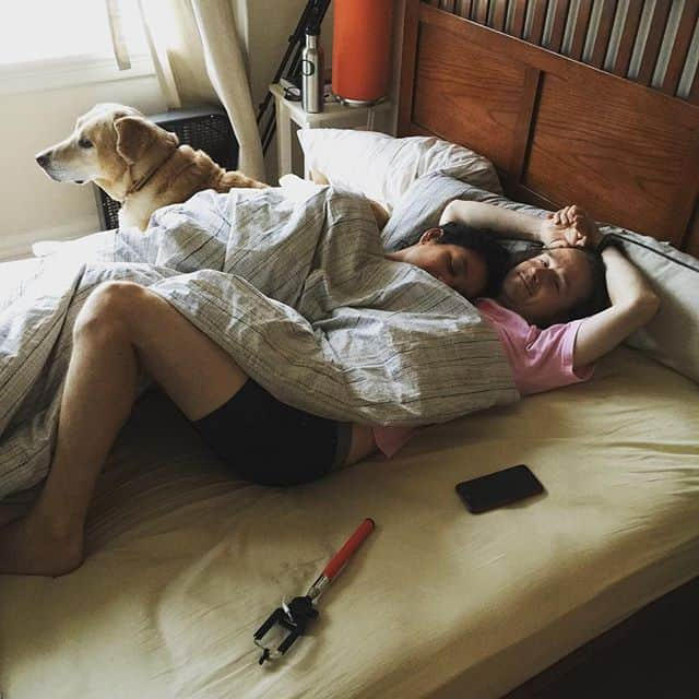 2 people and a dog laying in bed