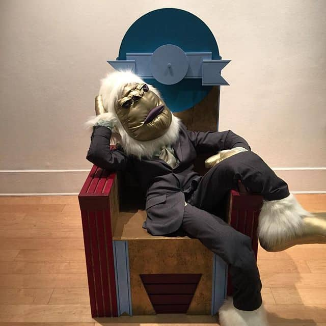 Politician lounging in a chair that resembles the Portland Building